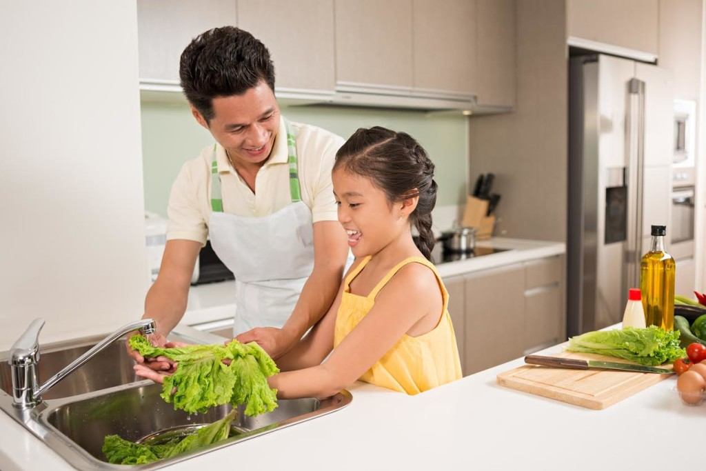 father and daughter washing fresh lettuce for the salad