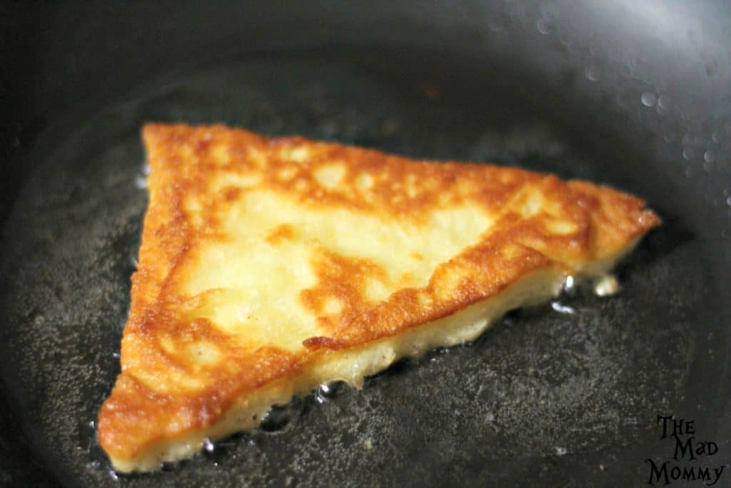 Heat about 1/4 cup of vegetable oil, in a medium sized skillet, to a low medium and drop a triangle of dough in. Let it sizzle for about 2 minutes and give it a flip.